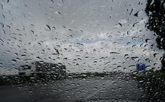 Look on truck on the highway through wet windshield with rain drops Stock Photos