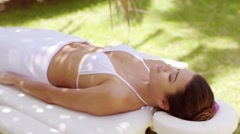 Single woman laying down in outdoor beauty spa Stock Footage