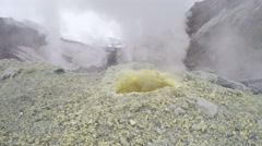 Steaming (smoking) fumarole on thermal field in crater active volcano - stock footage