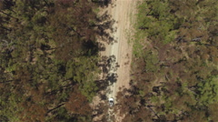 AERIAL: White SUV car driving along straight wide countryside road in forest Stock Footage