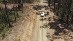AERIAL: White SUV car driving along dirt road leading through lush forest Stock Footage