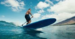 Surfer on blue ocean wave stand up paddle boarding - stock footage