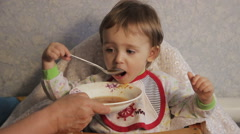 Grandmother feeds the child Stock Footage