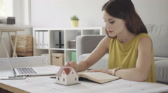 Female architect working from home over some bluerprints Stock Footage