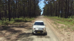 CLOSE UP: White SUV car driving fast along dry road leaving cloud of dirt behind Stock Footage