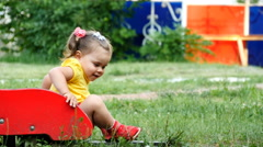 Little girl is laughing sitting on a children's slide - stock footage
