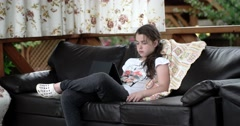 Girl Using Tablet Computer Lying on Leather Sofa on Terrace - stock footage
