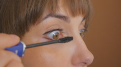 Pretty girl paints her upper eyelash. Closeup Stock Footage