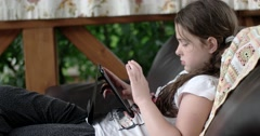 Little Girl Using Tablet Computer on Sofa on Terrace Stock Footage
