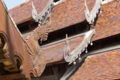 wooden naga sculpture on ancient buddhism temple roof - stock photo
