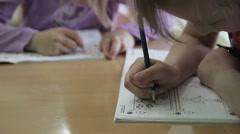 Children write in a notebook in kindergarten Stock Footage