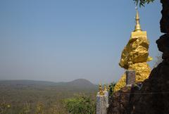 Golden buddhism pagoda on big stone Stock Photos