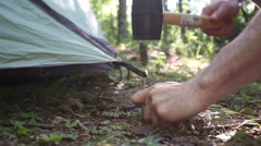 Hammering Tent Stake into Dirt on Sunny Camping Trip Stock Footage