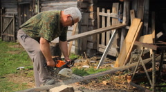 A man is cutting some wood using a chainsaw - stock footage