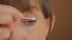 Young lady removes excess paint from upper eyelid - stock footage