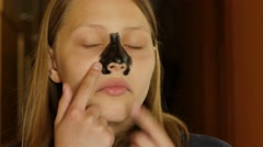 Facial Treatment. Teen girl cleaning pores of her nose with a mud mask. 4K UHD Stock Footage