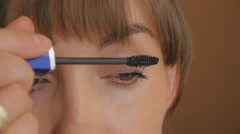 Pretty girl finishes of painting her upper eyelash. Closeup - stock footage