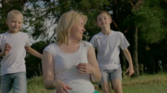 Family in the summer sunny day in the park. Children playing with their parents - stock footage