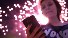 Girl use smart phone , image of firework as a background. Stock Footage