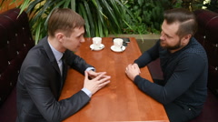 Handsome two businessmen have a meeting in cafe. tense men - stock footage