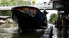 Public transport boat arriving at the pier on the canal Stock Footage