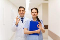 doctor and nurse showing ok sign at hospital - stock photo