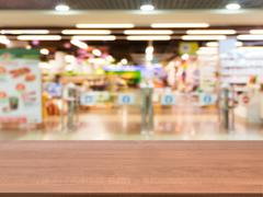 Wooden empty table in front of blurred supermarket Stock Photos
