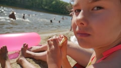 Teen girl eats a sandwich on beach holiday vacation slow-motion video Stock Footage