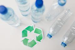 close up of plastic bottles and recycling symbol - stock photo