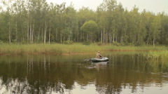 Man fisherman floats on a lake on an inflatable boat. Early morning - stock footage