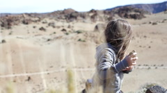 Girl holds volcanic rocks in the mountains of Tenerife Stock Footage
