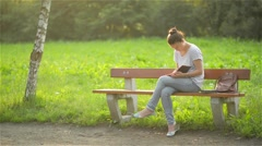 Beautiful young woman is writing a diary outdoors in the park, student studying Stock Footage