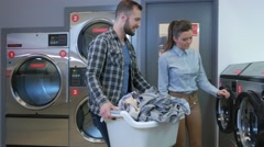 Young cheerful couple doing laundry together at laundromat shop in 4k UHD video. Stock Footage