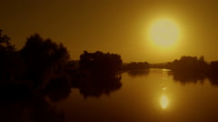 Panorama with river, golden sun and reflection in water, drone shot by Pakito. Stock Footage