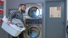 Handsome man doing laundry at laundromat shop in 4k UHD video. Stock Footage
