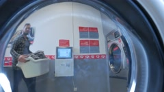 Handsome man doing laundry at laundromat shop in 4k UHD video. - stock footage