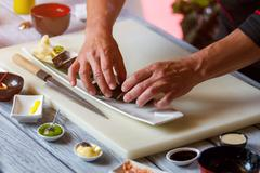 Man's hands touch sushi rolls. Stock Photos