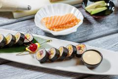 Bowl with sauce beside sushi. Stock Photos
