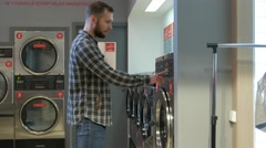 Young cheerful couple doing laundry together at laundromat shop in 4k UHD video. - stock footage