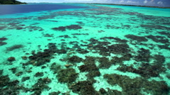 Aerial view of tropical turquoise lagoon and reef Bora Bora Island South Pacific Stock Footage