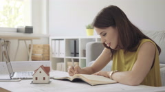 Young woman working from home over some blueprints planning home design Stock Footage