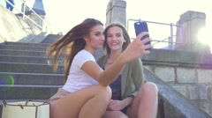 2 in 1 video. Two young girl sitting on the stairs and taking selfie. Stock Footage