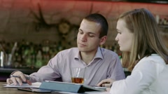 Half length of young business man and woman sitting in a bar discussing Stock Footage
