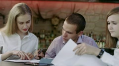 Half length of young business man and women sitting in a bar discussing Stock Footage