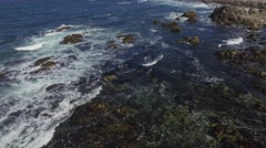Low Altitude moving aerial drone shot of Pebble Beach shoreline and rocks Stock Footage