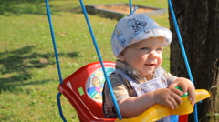Happy baby boy having fun on a swing ride at a playground a summer day. Baby Stock Footage