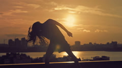 Young attractive girl with flowing hair doing the dance moves at sunset Stock Footage