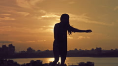 Young attractive girl with flowing hair dancing movements of Kupwara at sunset Stock Footage