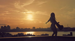 Young attractive girl with flowing hair over the sun dancing the movement of Stock Footage