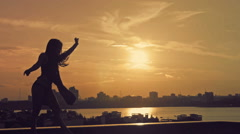 Young attractive girl with flowing hair dancing acrobatic flip at sunset Stock Footage